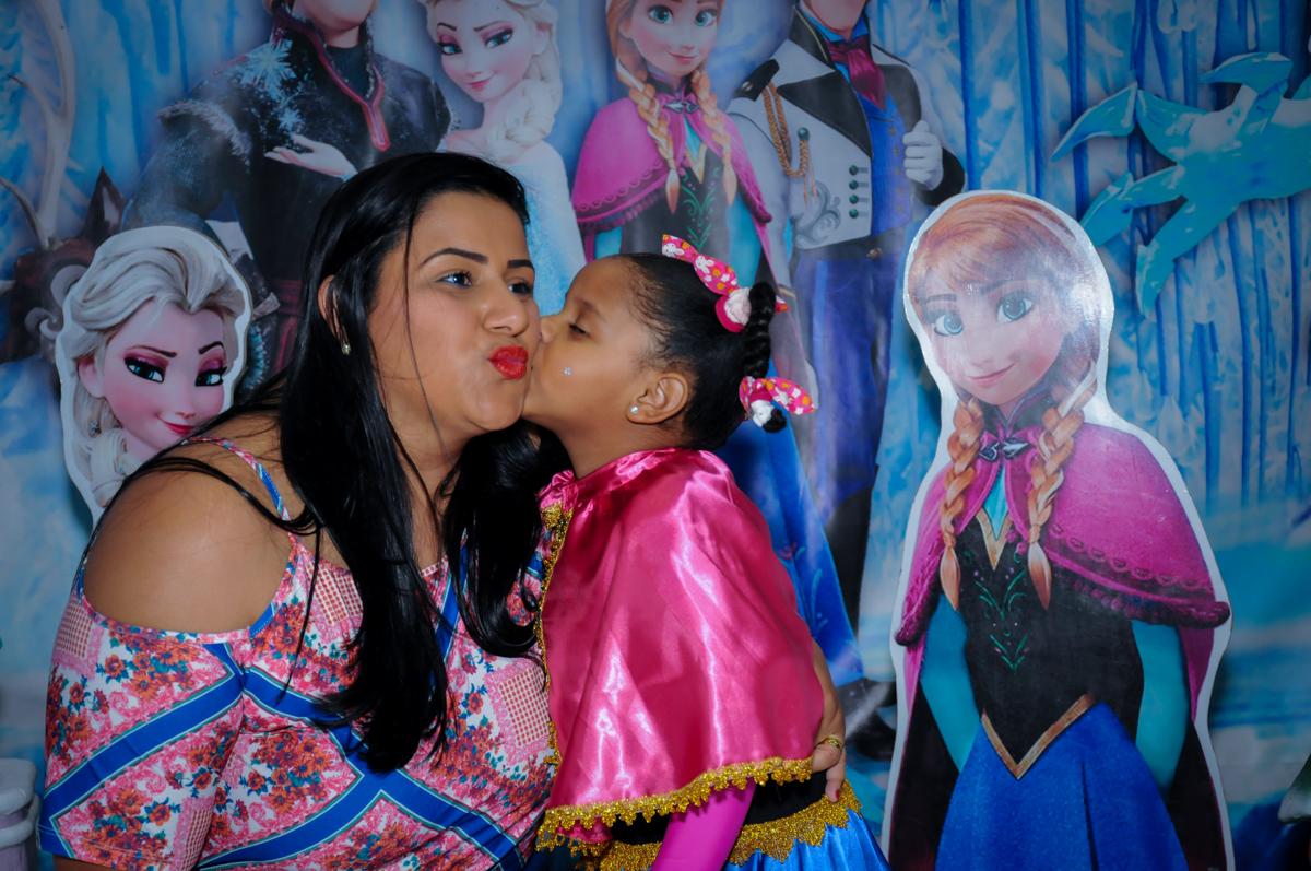 beijinho da aniversariante em sua mãe em frente a mesa frozen no Buffet Magic Joy Unidade Saude