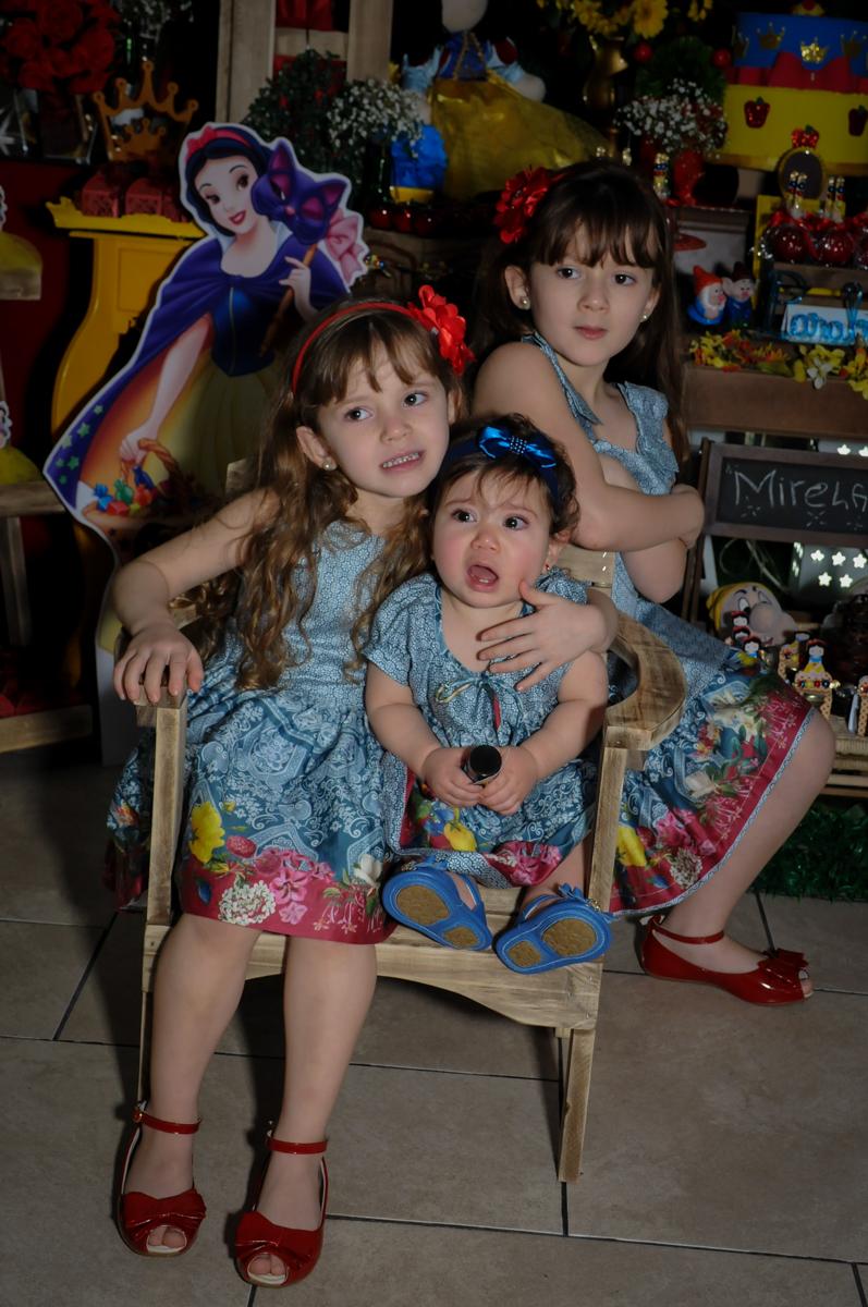 foto da aniversariante e suas irmãs na mesa decorada branca de neve no Buffet Ciranda da Vila, Osasco, SP