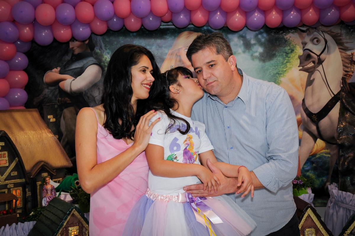 beijinho da aniversariante em seu pai em frente a mesa tema rapunzel no Buffet Fábrica da Alegria Osasco, São Paulo