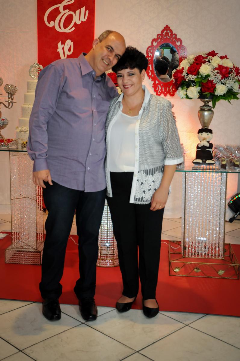 foto do casal em frente a mesa decorada bodas de prata no Buffet Fábrica da Alegria, osasco, sp