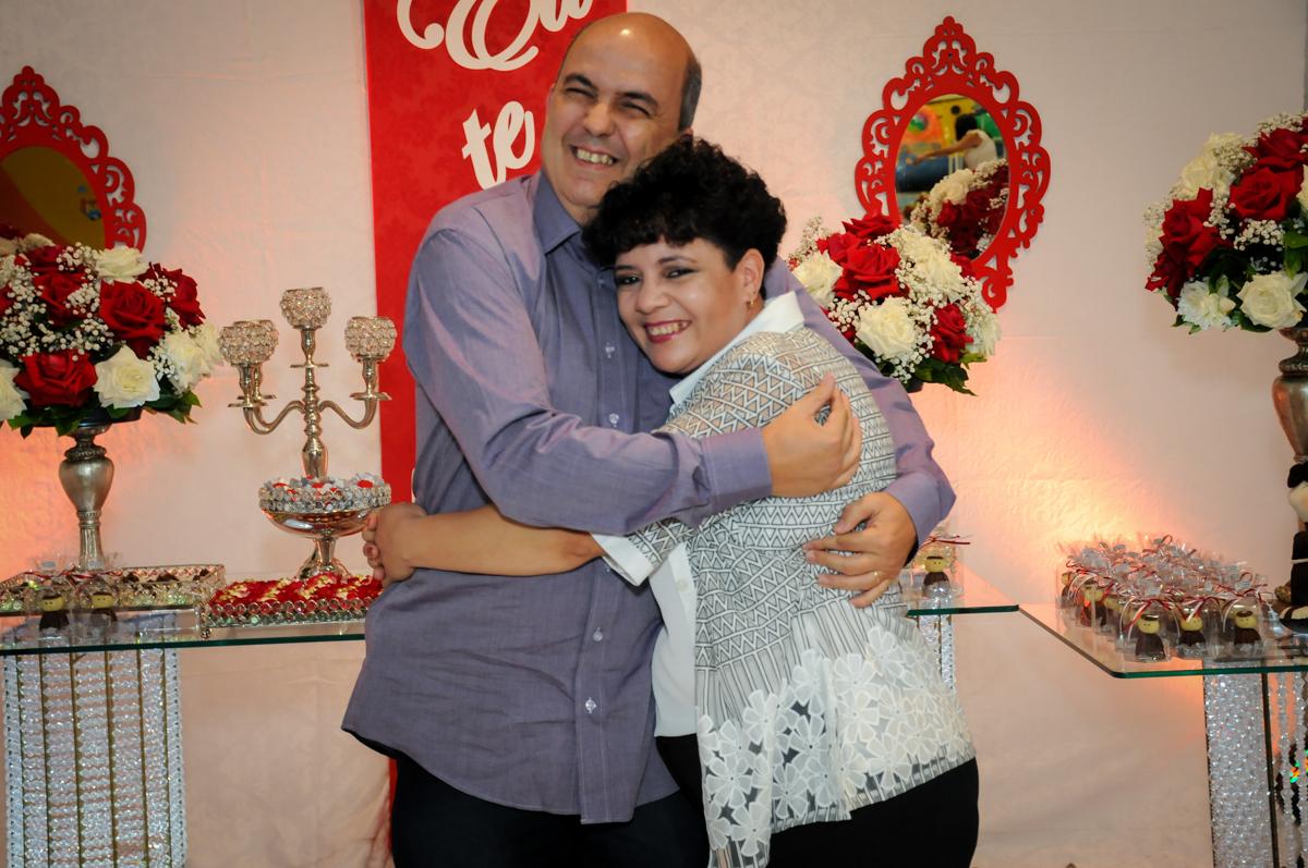 abraço do casal em frente a mesa decorada bodas de prata no Buffet Fábrica da Alegria, osasco, sp