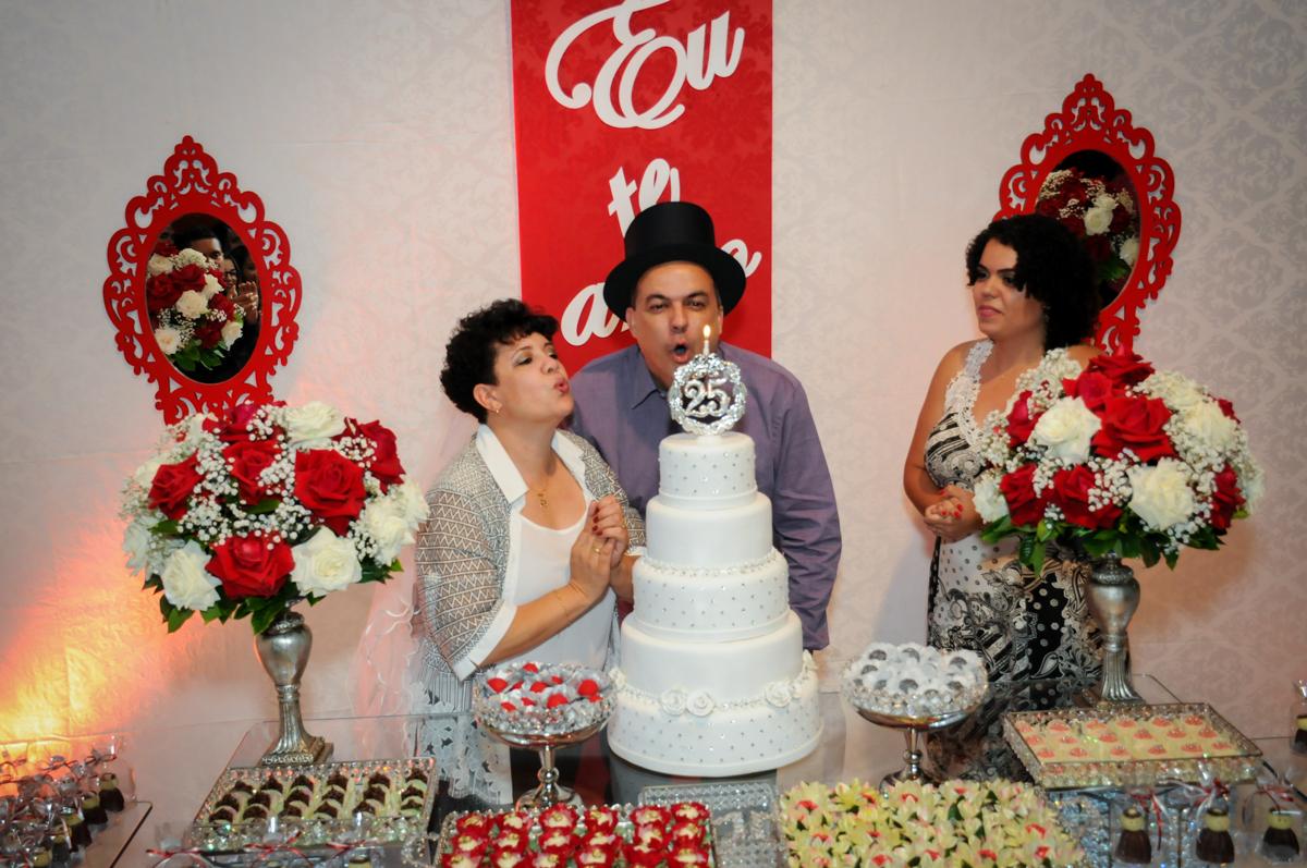 assoprando a velinha do bolo na festa de 25 anos de casados do casal no  Buffet Fábrica da Alegria, osasco, sp