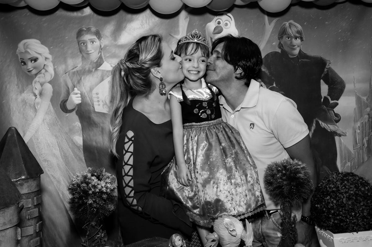 os pais dão beijo sanduiche na aniversariante em frente a mesa decorada tema frozen no Buffet Infantil Hary Happy, Morumbi, São Paulo