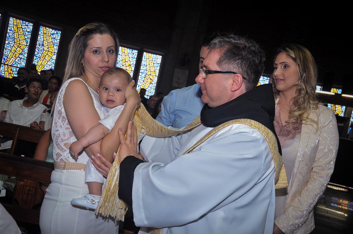 O padre faz o sinal da cruz no peito do Matheus no Paróquia São Bento Morumbi