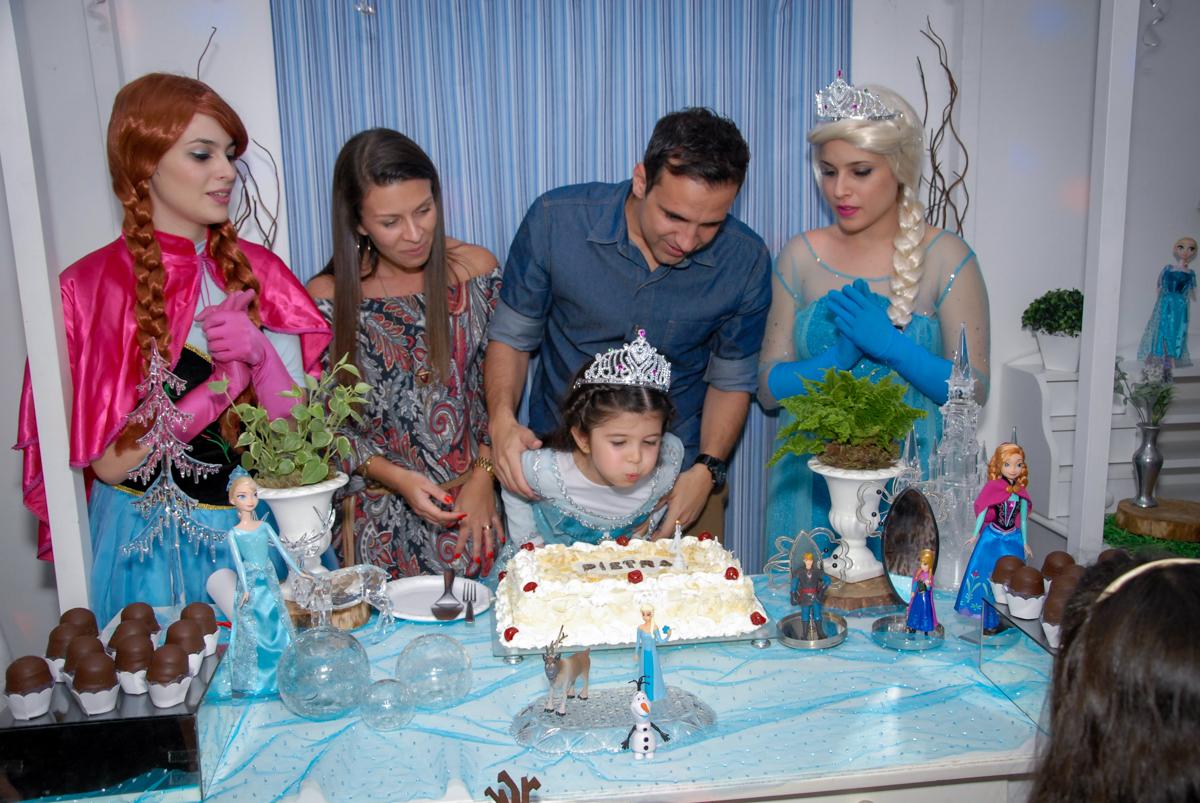 aniversariante assopra a velinha do bolo no  buffet feliz da vida, butantã,sp