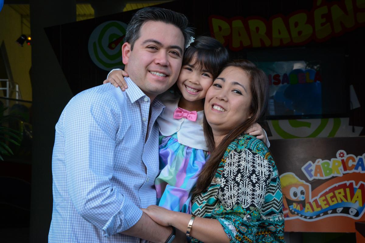 foto da aniversariante com seus pais em baixo do arco de bexigas no Buffet Fábrica da Alegria, Morumbi, SP