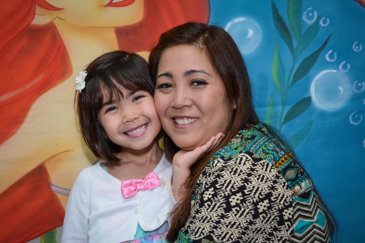foto da aniversariante com sua mãe em frente a mesa decorada ariel no Buffet Fábrica da Alegria, Morumbi, SP