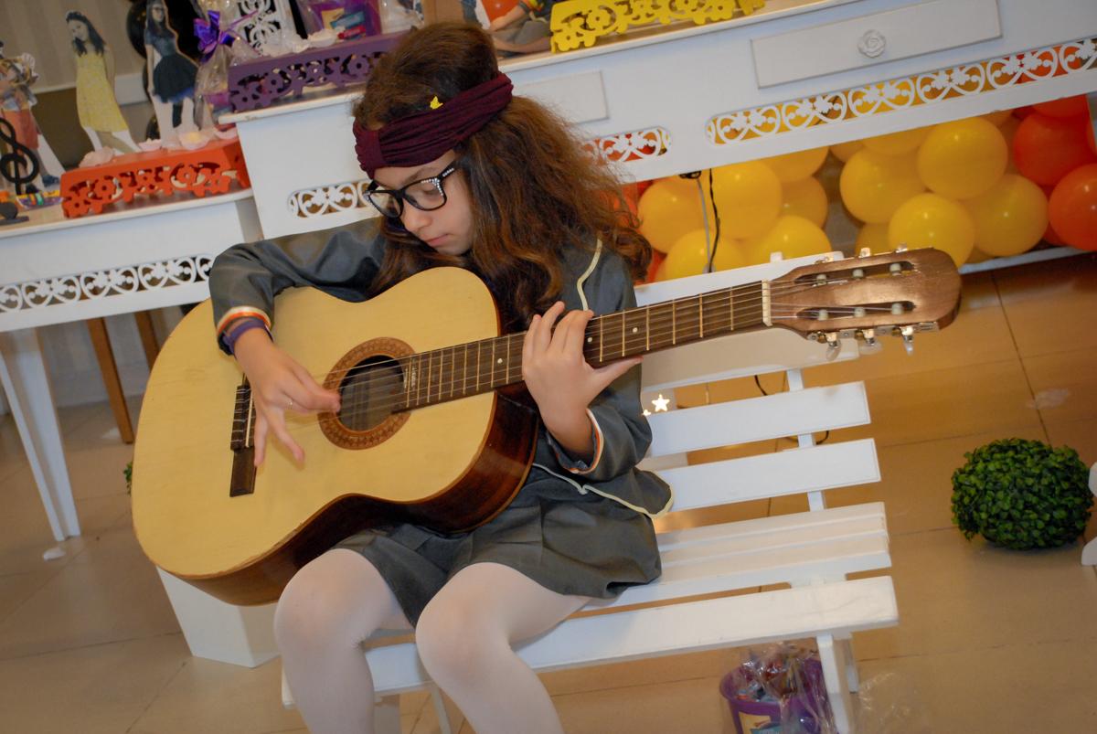 final da festa com a aniversariante tocando violão no Condomínio em Alphaville