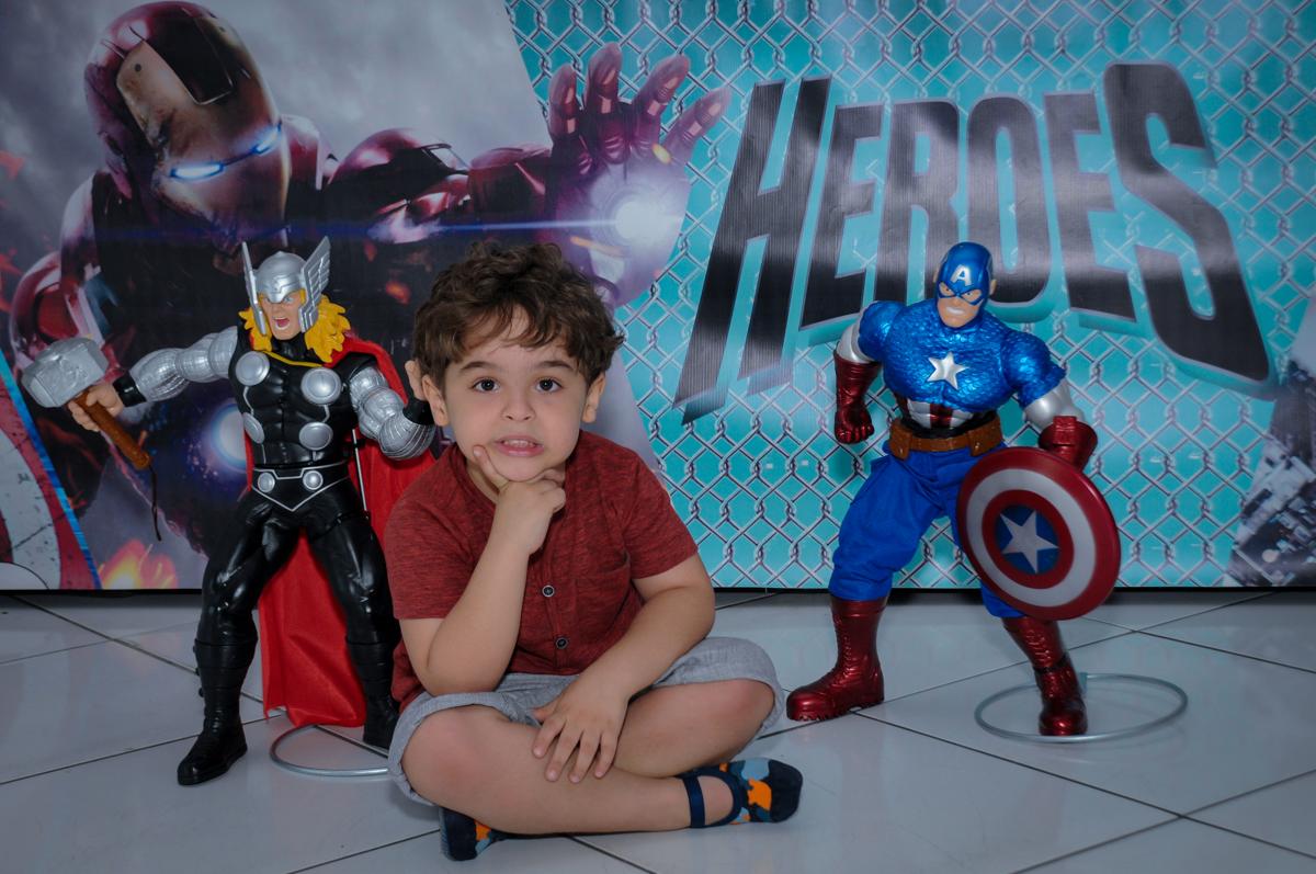 O aniversariante posando para foto em frente a mesa decorada super heróis no Buffet Fábrica da Alegria Morumbi