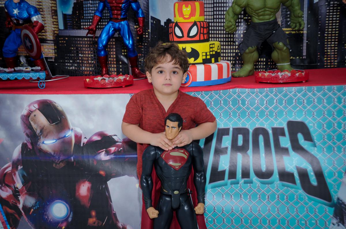 Foto do Enrico com o super homem em frente a mesa decorada super heróis no Buffet Fábrica da Alegria Morumbi