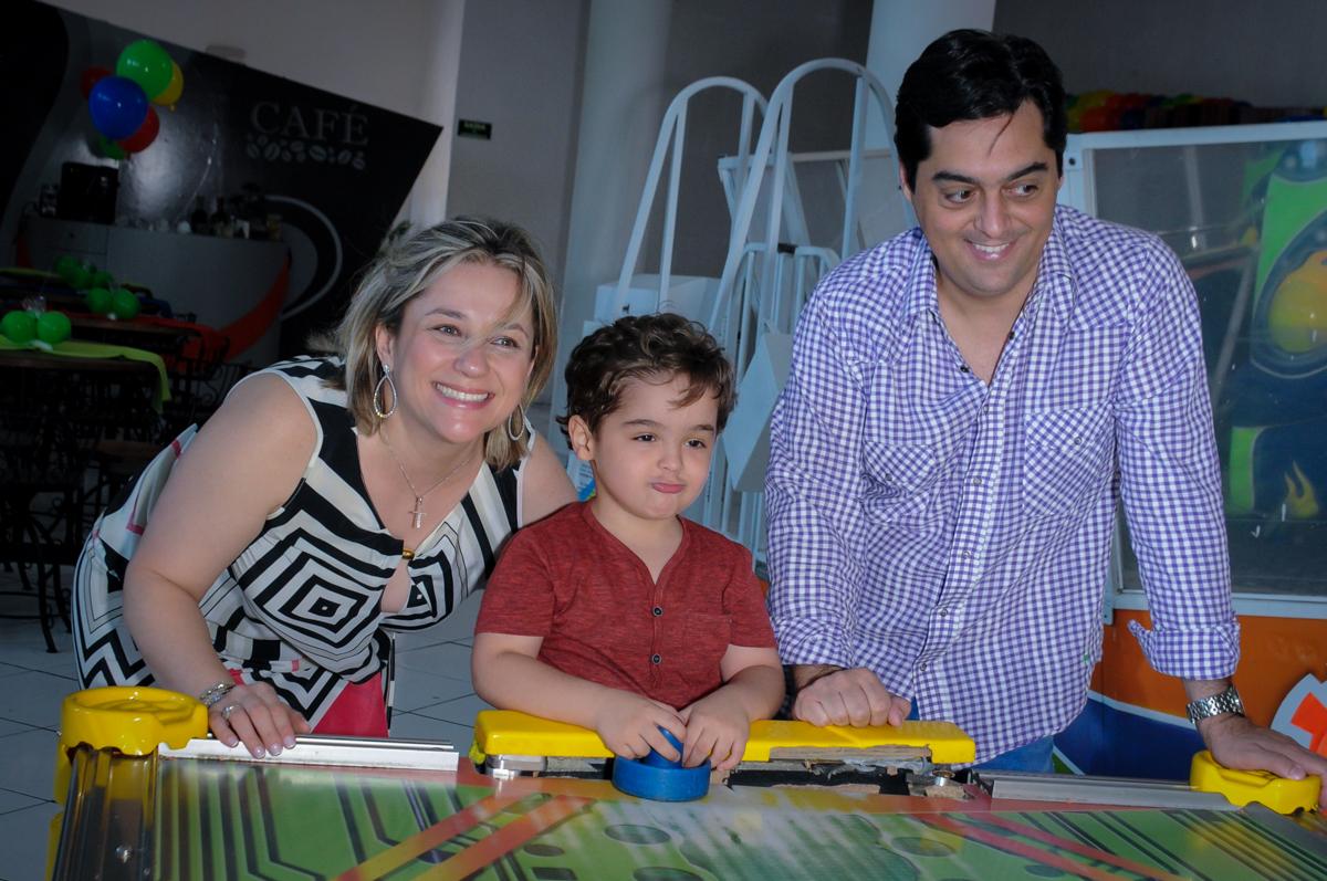 Enrico joga futebol de mesa com seus pais no Buffet Fábrica da Alegria Morumbi