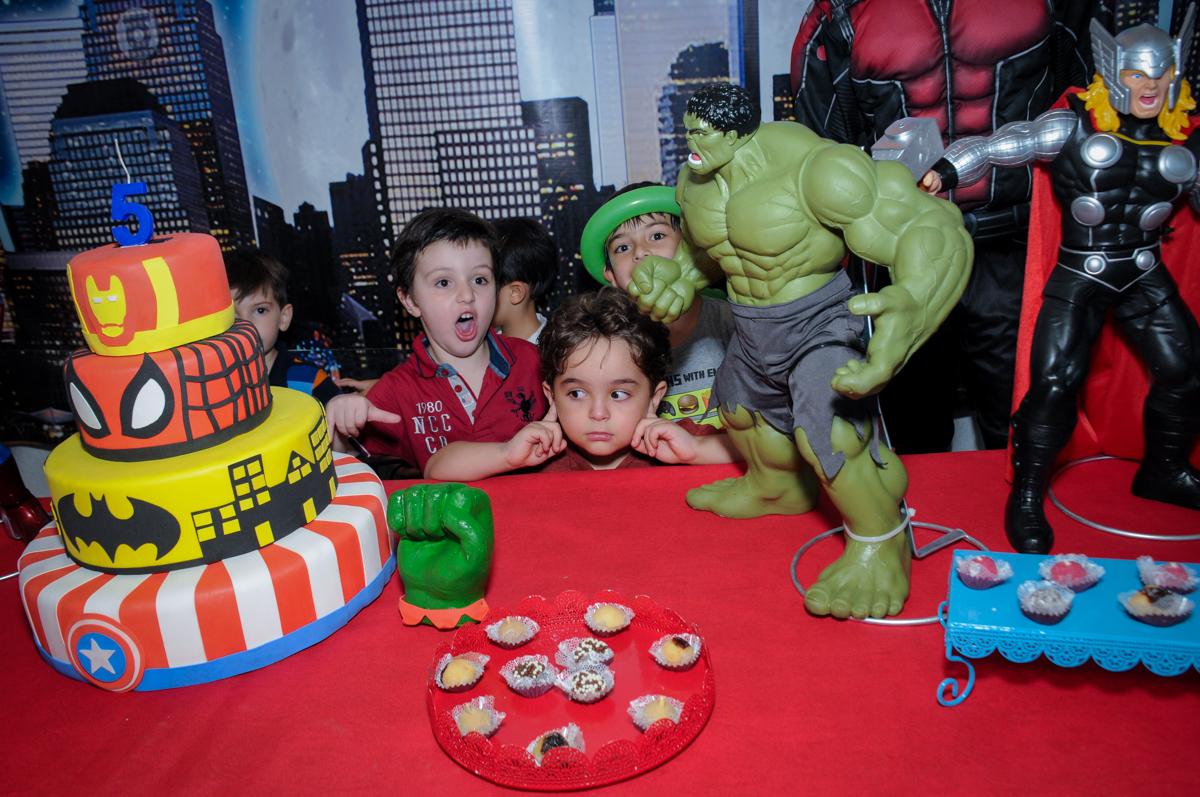 A criançada em frente a mesa decorada super heróis para cantar o parabéns no Buffet Fábrica da Alegria Morumbi