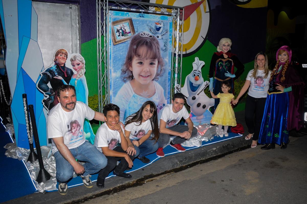 família sendo fotografada na fachada do buffet no Buffet Fábrica da Alegria, Morumbi