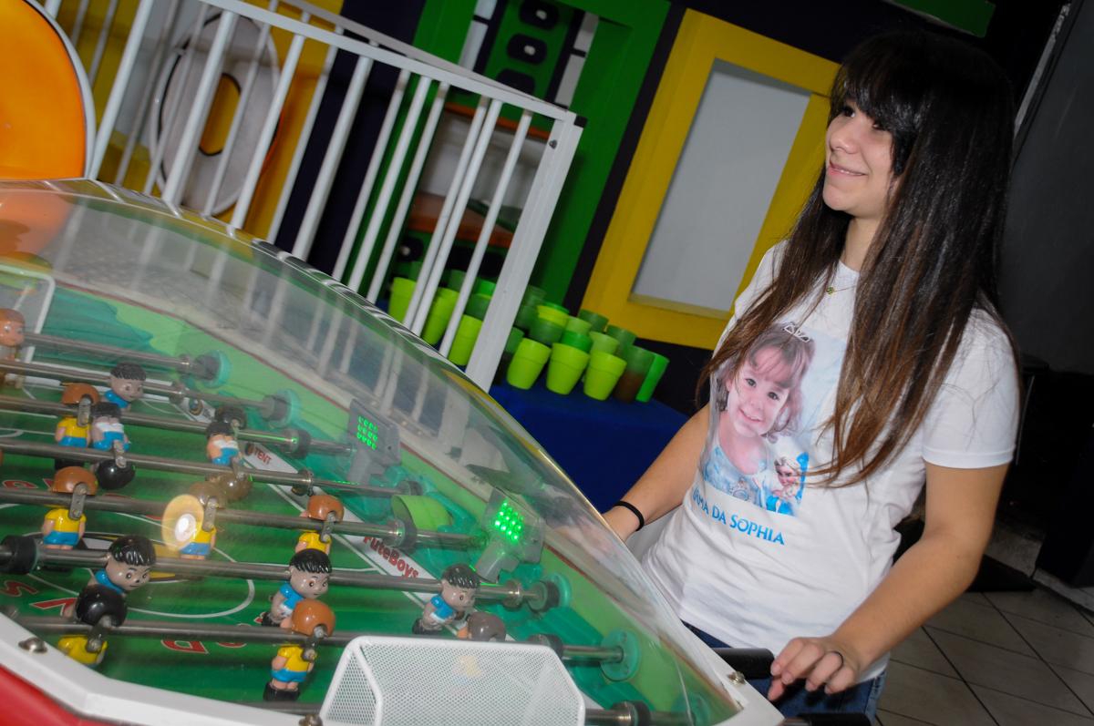 irmã da aniversariante brinca no pebolim no Buffet Fábrica da Alegria, Morumbi