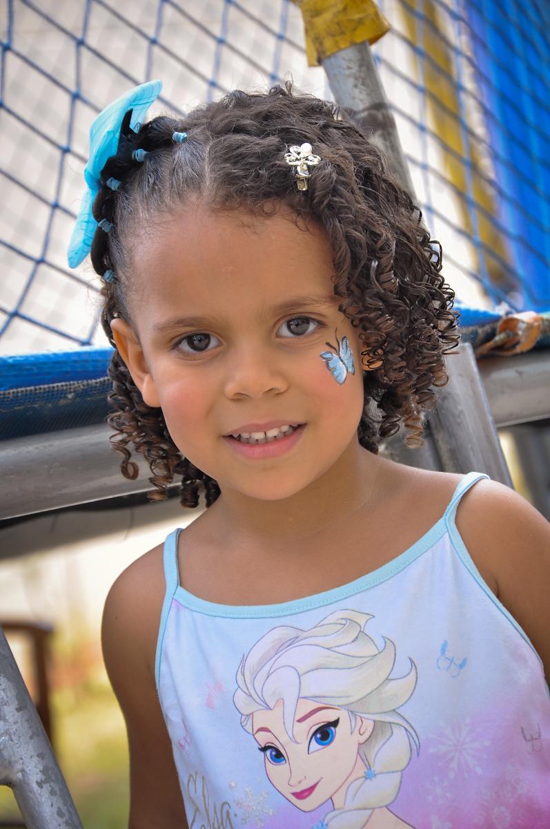 a aniversariante faz pintura de uma borboleta no Condomínio São Paulo, SP, tema da festa Frozen