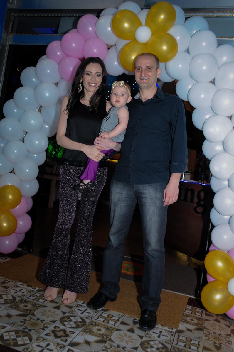 foto da aniversariante com seus pais embaixo do arco de bexigas no buffet amazing, alphaville,sp, tema da mesa bonecas princesas