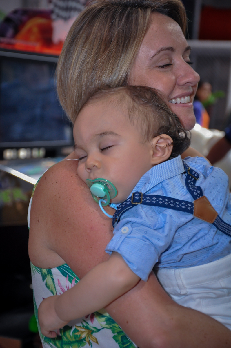 O aniversariante dorme no ombro da convidada no Buffet Fábrica da Alegria, Osasco, festa do Levi 1 aninho, tema da festa Bob zoom