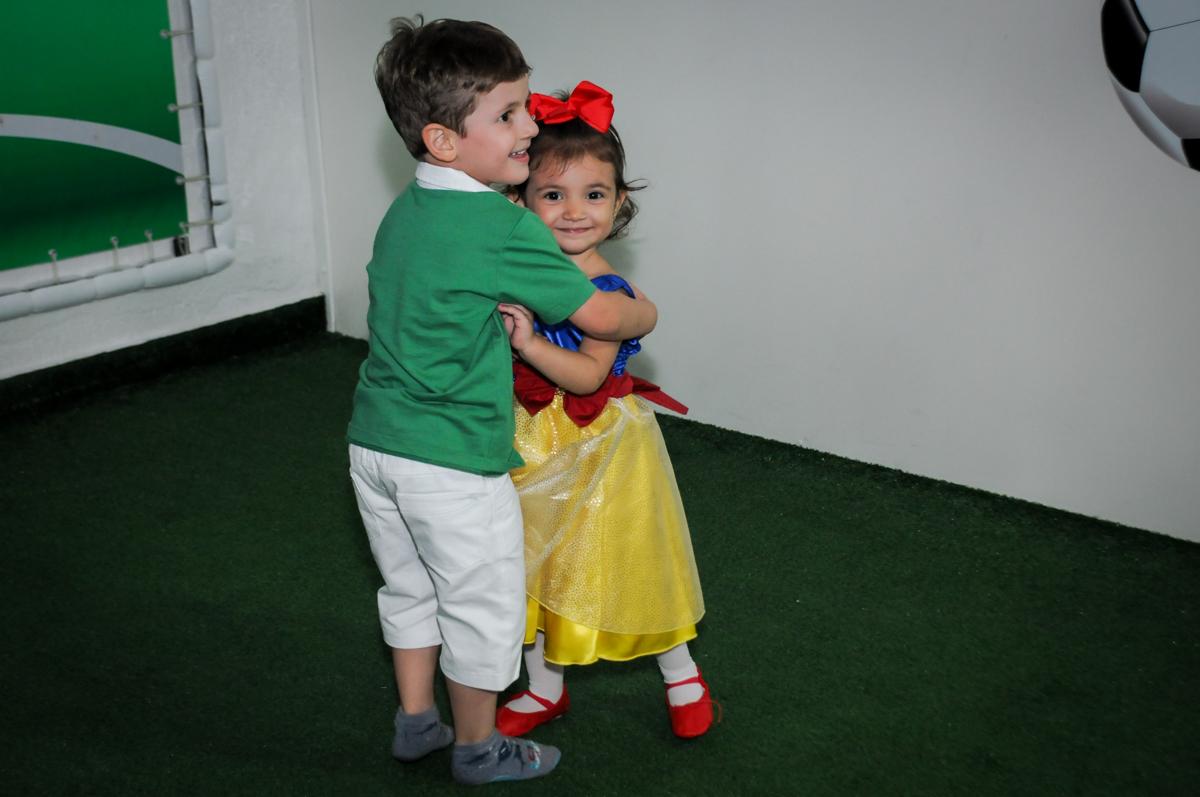 abraço do amiguinho no campo de futebol na aniversário infantil, nathália 2 anos,tema da mesa branca de neve, buffet magic joy, moema, sp