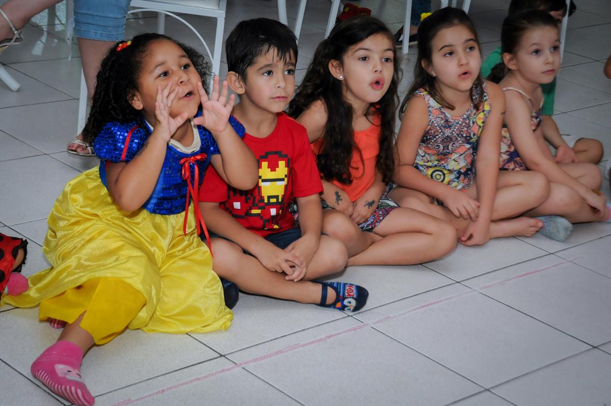as crianças ficam atentas ao show do mágico no Buffet Paparicos, festa infantil, tema da mesa dinossauros, guilherme 5 anos