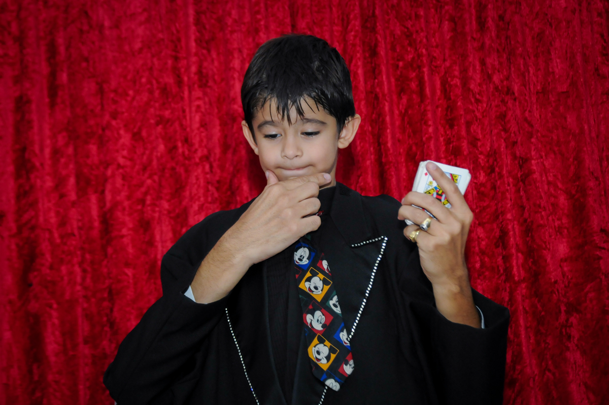 o aniversariante fazendo mágica com as cartas de baralho no Buffet Paparicos, festa infantil, tema da mesa dinossauros, guilherme 5 anos
