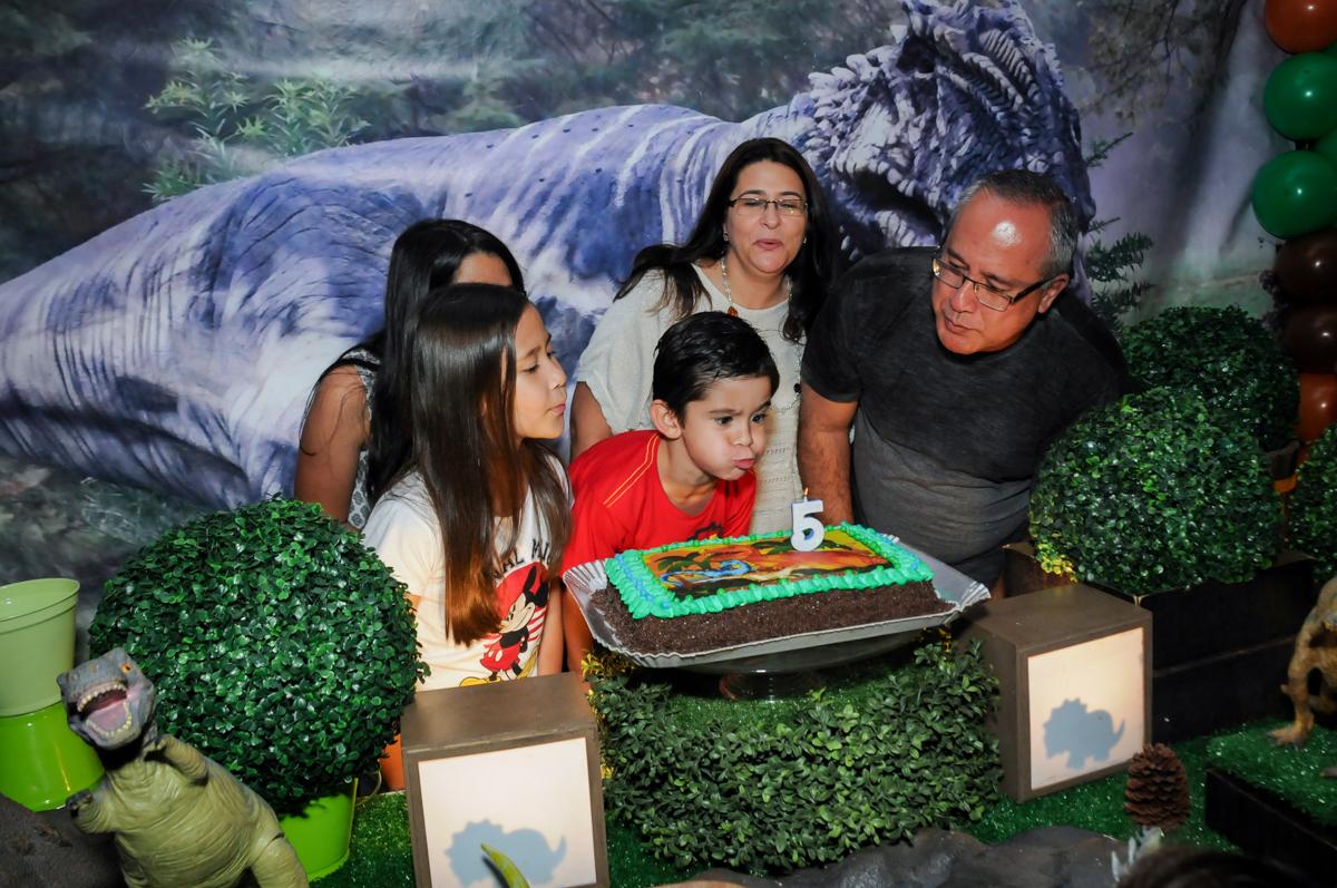 assoprando a velinha do bolo no Buffet Paparicos, festa infantil, tema da mesa dinossauros, guilherme 5 anos