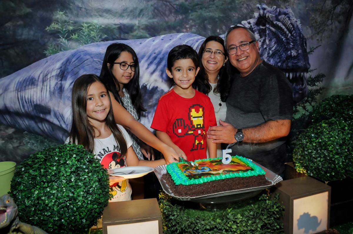 cortando o primeiro pedaço de bolo no Buffet Paparicos, festa infantil, tema da mesa dinossauros, guilherme 5 anos