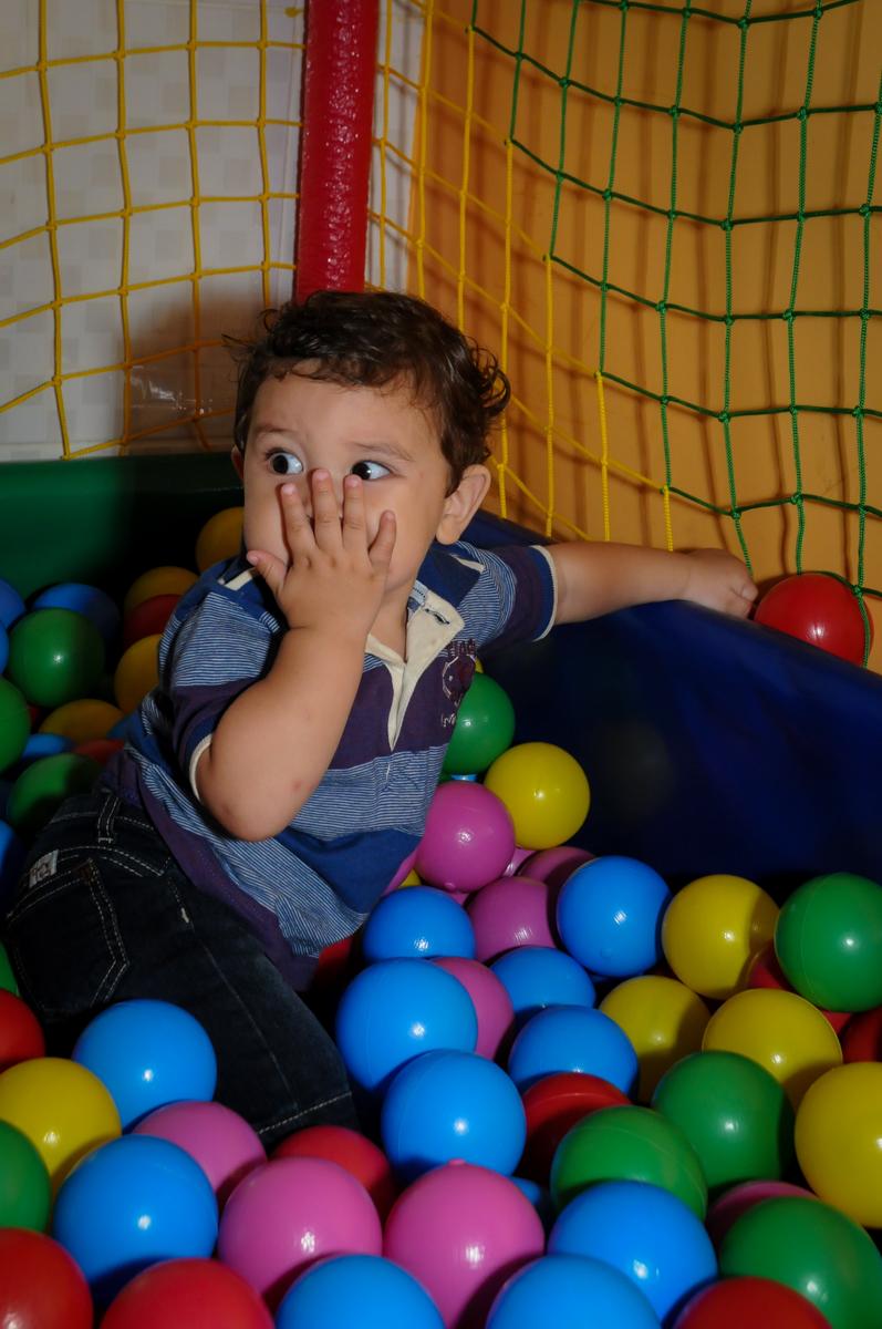 o aniversariante joga beijinho enquanto brinca na piscina de bolinha na Festa Infantil, no condominio Osaco, SP, tema Galinha Pintadinha, Pietro 1 aninho