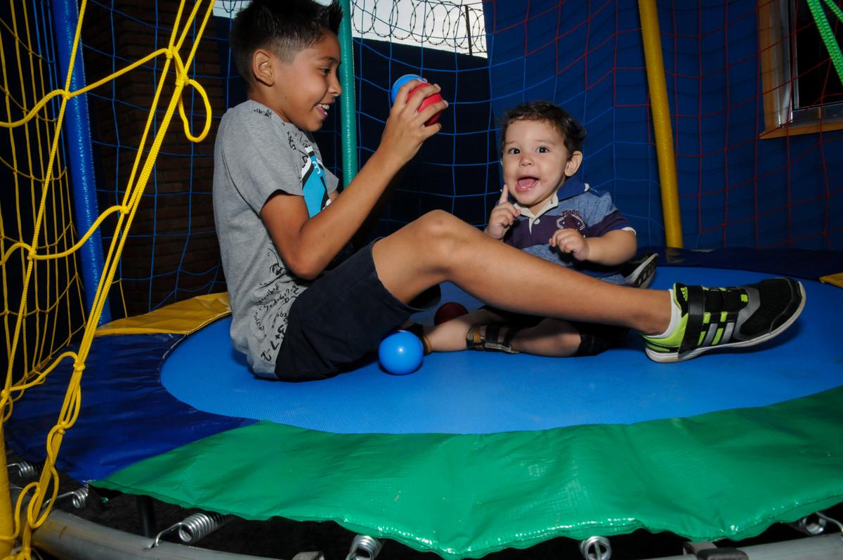 o aniversariante brinca com o irmao na cama elastica na Festa Infantil, no condominio Osaco, SP, tema Galinha Pintadinha, Pietro 1 aninho