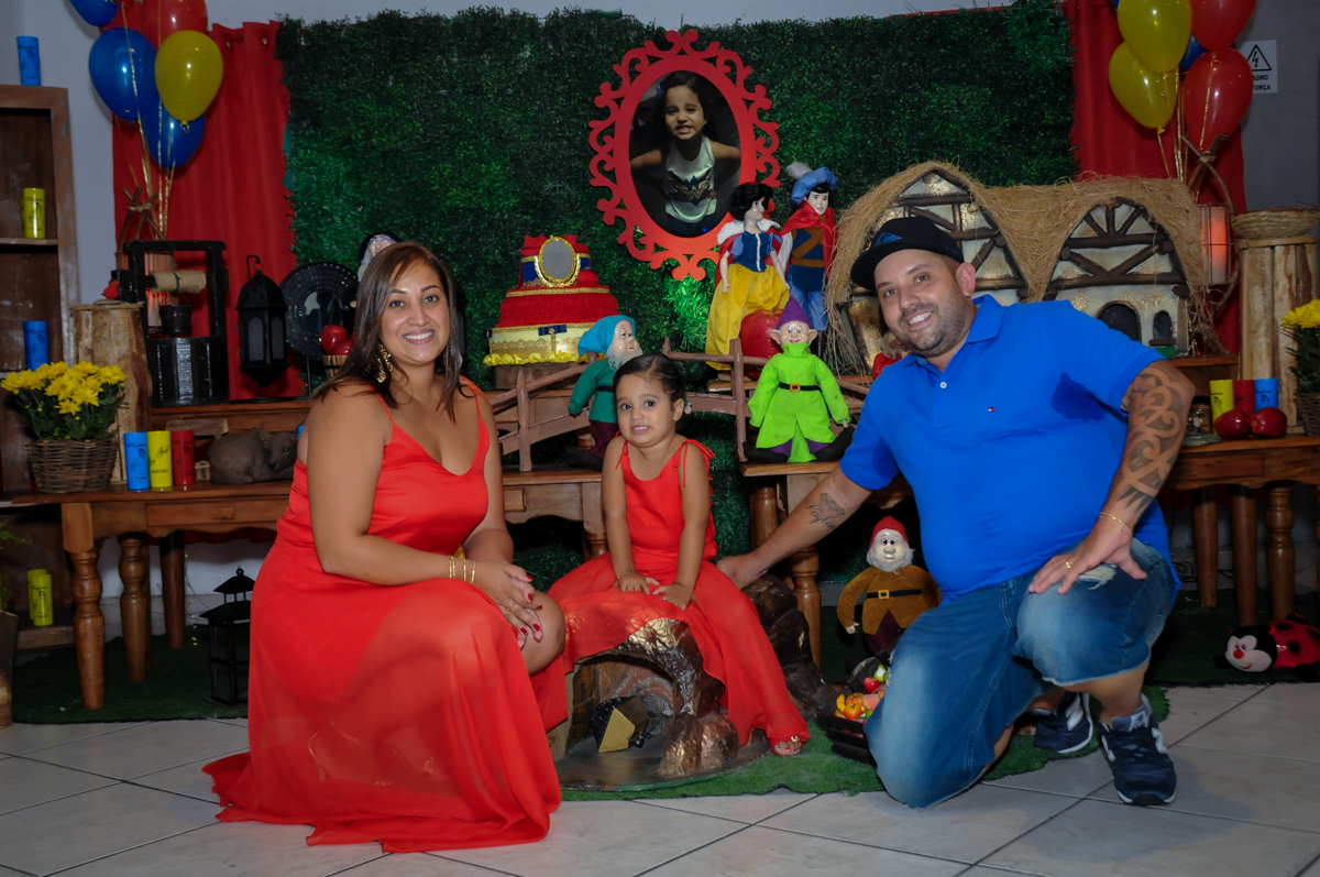 família sendo fotografada em frente a mesa do bolo no Buffet Fábrica da Alegria, festa infantil, tema da mesa branca de neve aniversarinte Kaylane 3 aninhos