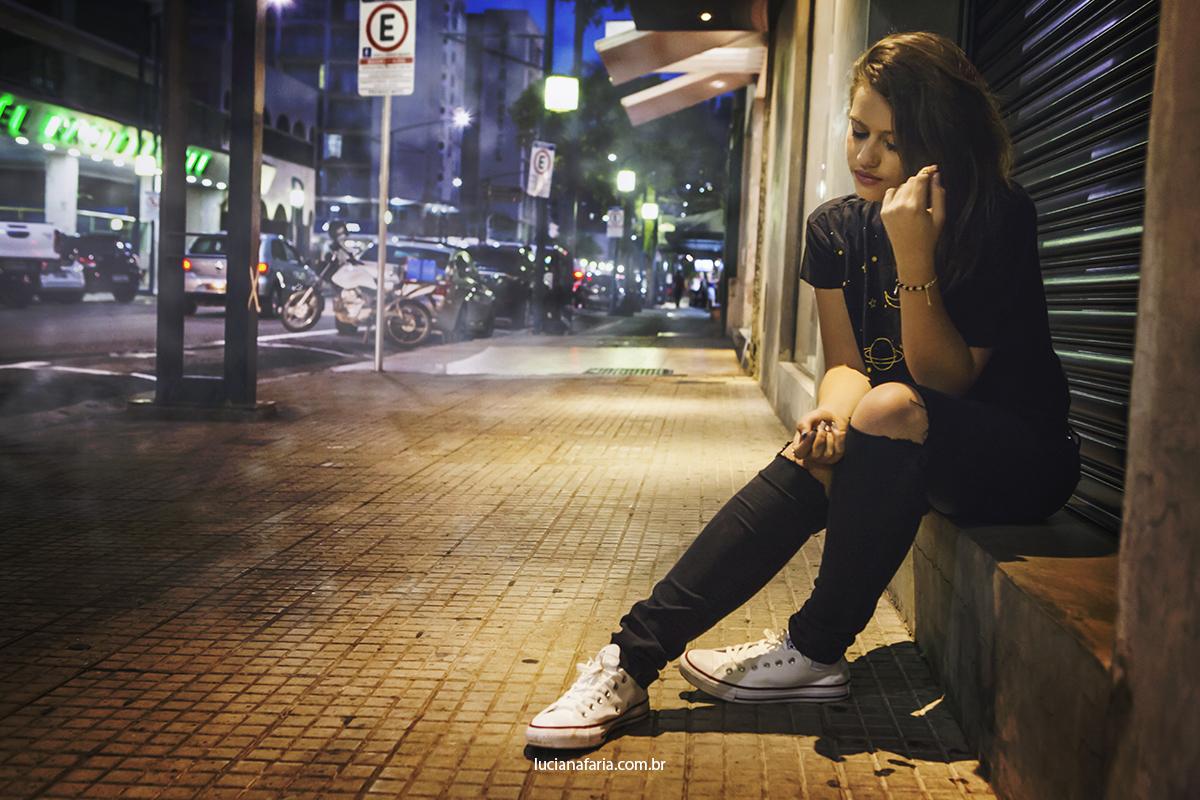 fotos menina sentada na calçada no centro da cidade em poços  fotografia de rua noturna