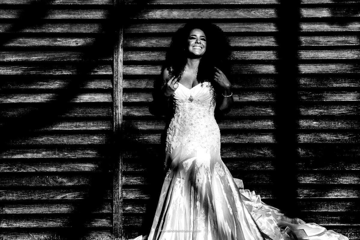 Noiva linda e seus cachos em uma belissima fotografia preto e branco, com um sorriso estonteante.