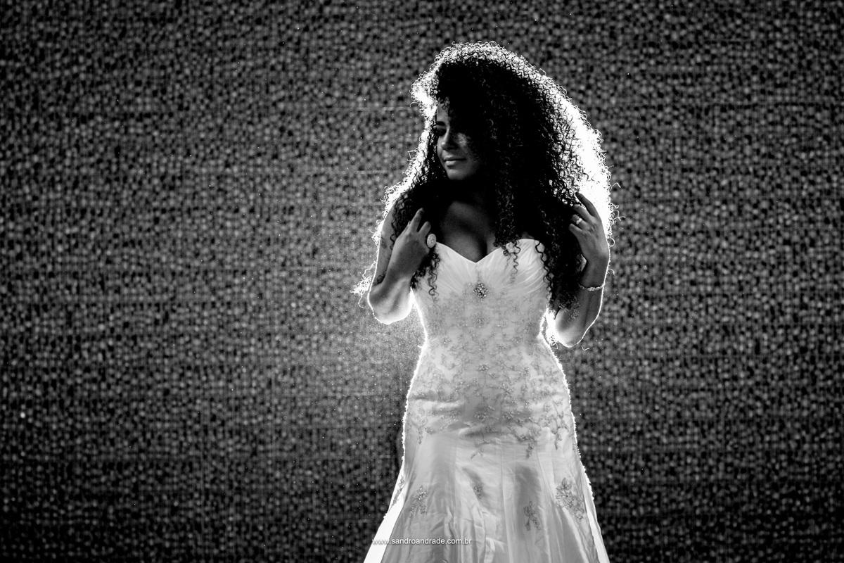 Retrato de noiva em preto e branco, a noiva e suas curvas, cachos e vestido branco, com uma belissima luz de fundo.