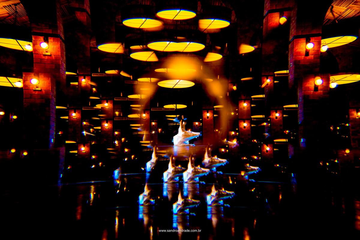 Mais uma fotografia colorida em tons vibrantes, noiva feliz girando no centro do salão e reflexos encantadores feito com cristal.
