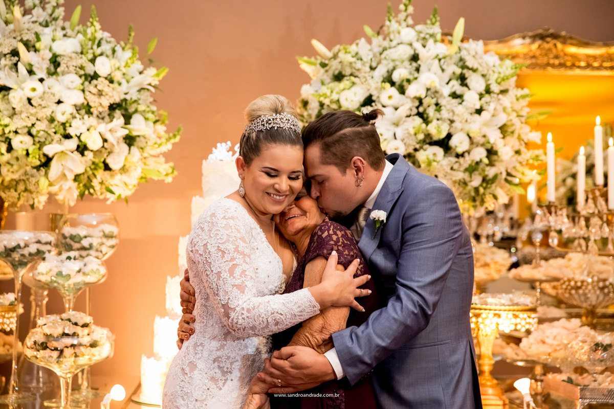 Os noivos afagam e beijam carinhosamente sua avó.