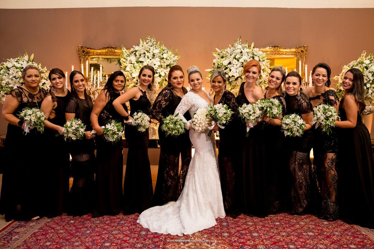 A noiva e as madrinhas, ela de branco linda e radiante e as madrinhas belas damas de preto.