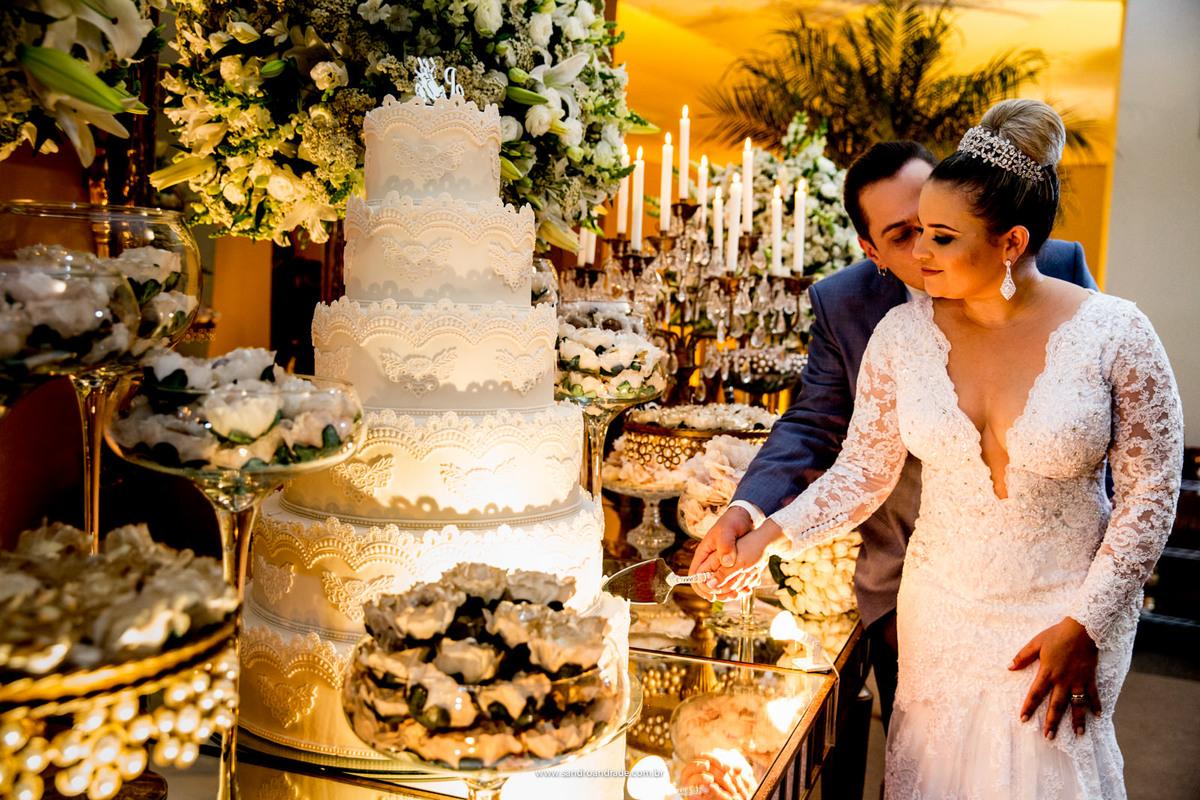 Linda fotografia do corte do bolo, o noivo beija o rosto de sua amada.