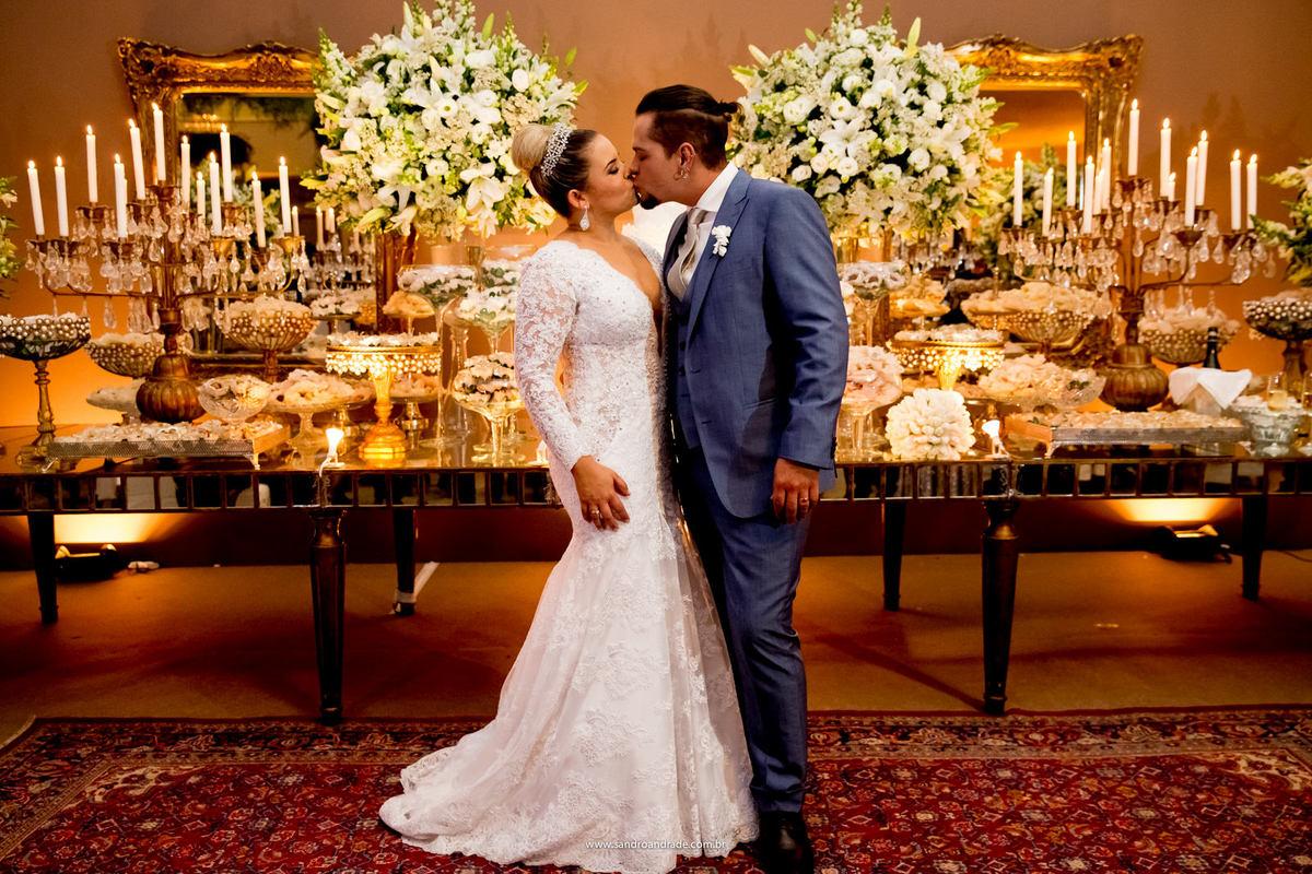 Belissima decoração da mesa do bolo, os noivos a frente se beijam, felizes.