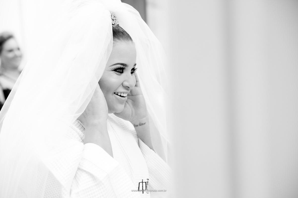 A noiva admirando sua maquiagem e seu véu de noiva em frente ao espelho.