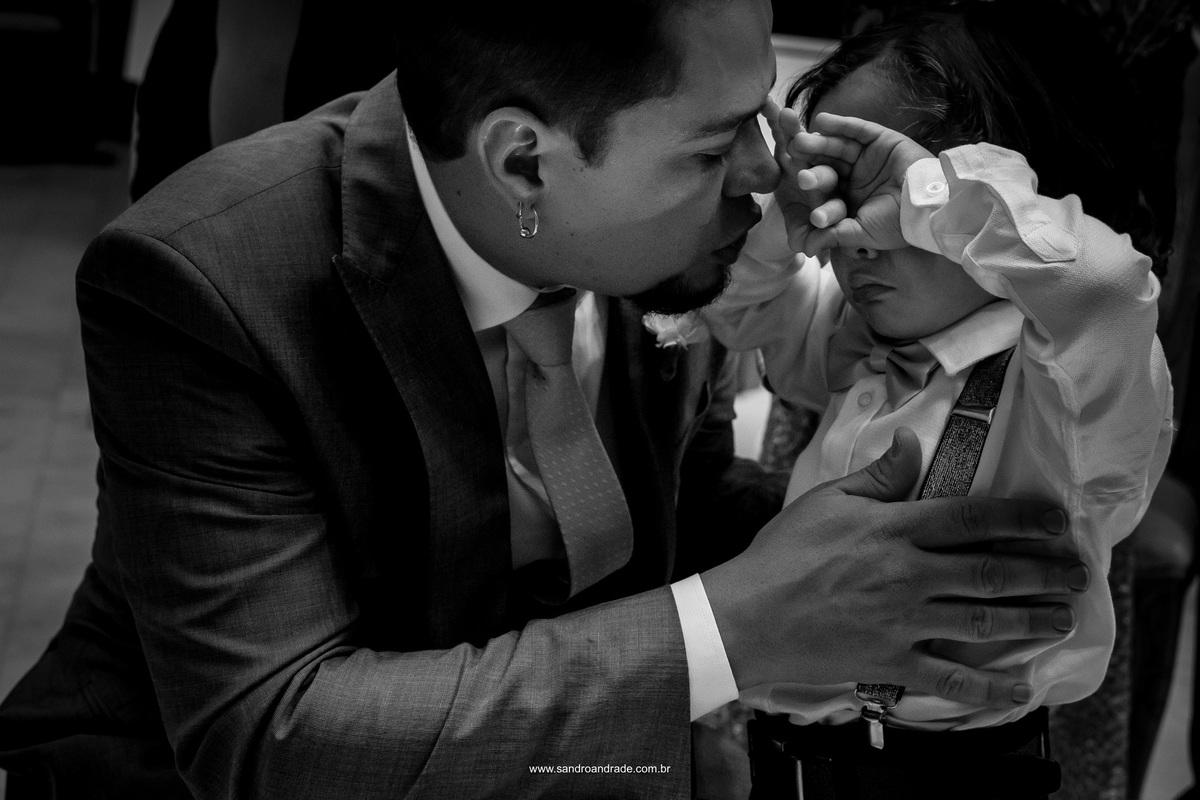 O noivo recebe seu filho no altar da igreja em uma linda fotografia preto e branco.