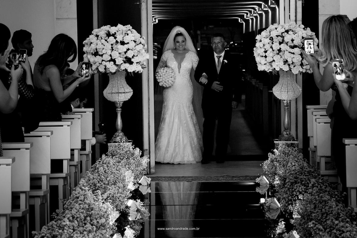 La vem a noiva, toda linda vestida de branco e um longo véu, de braço dado com seu pai.