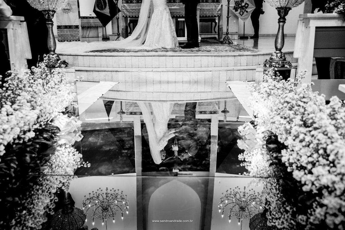 Fotografia de detalhes, reflexos dos noivos no altar com a linda decoração da igreja e troca de alianças.