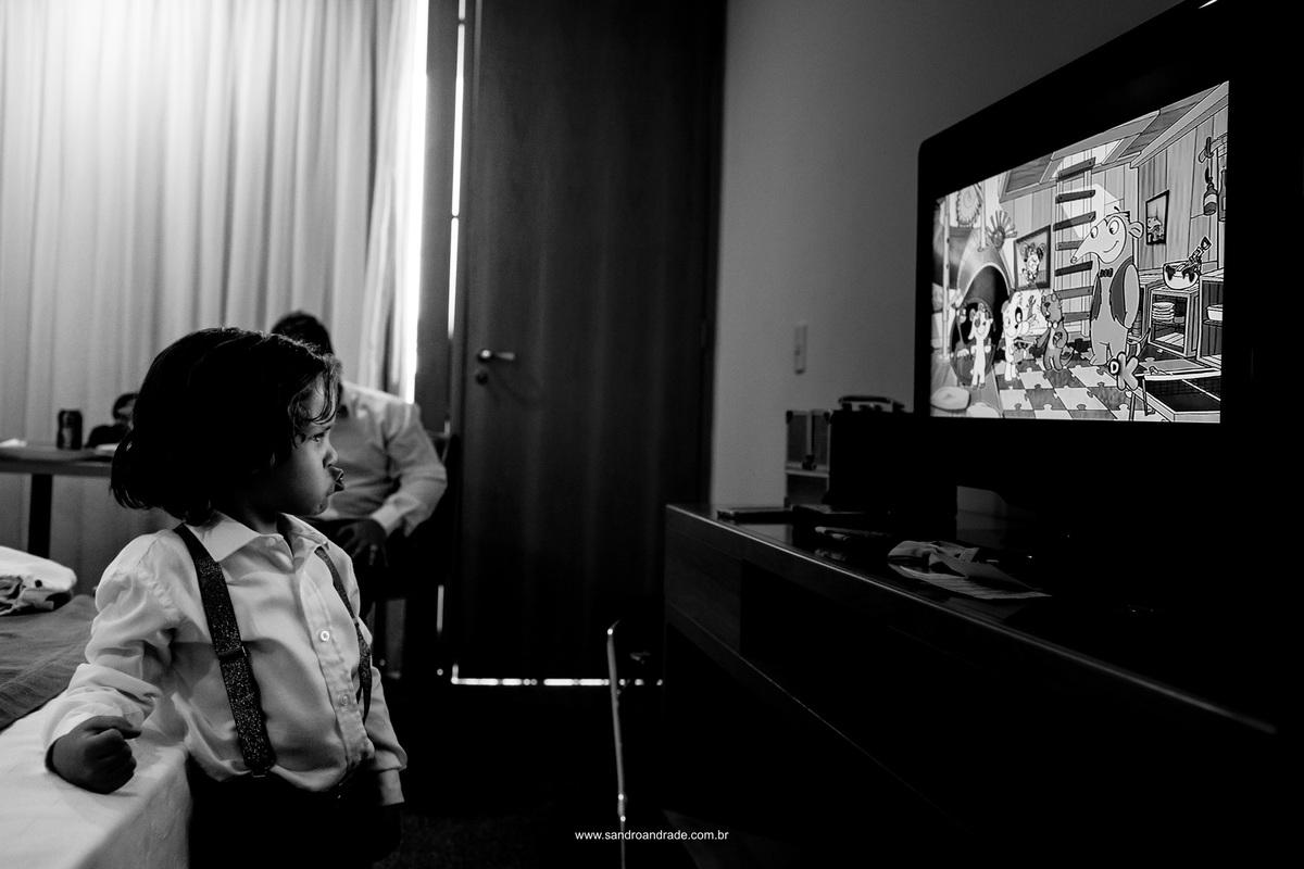 O lindo filho dos noivos assistindo   desenho enquanto seu pai se arruma para o grande momento.