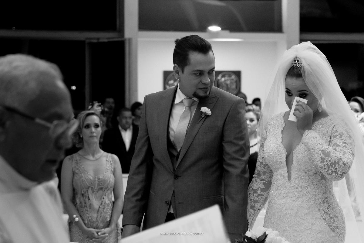 Noivos no altar, com um lindo registro em preto e branco da noiva emocionada.
