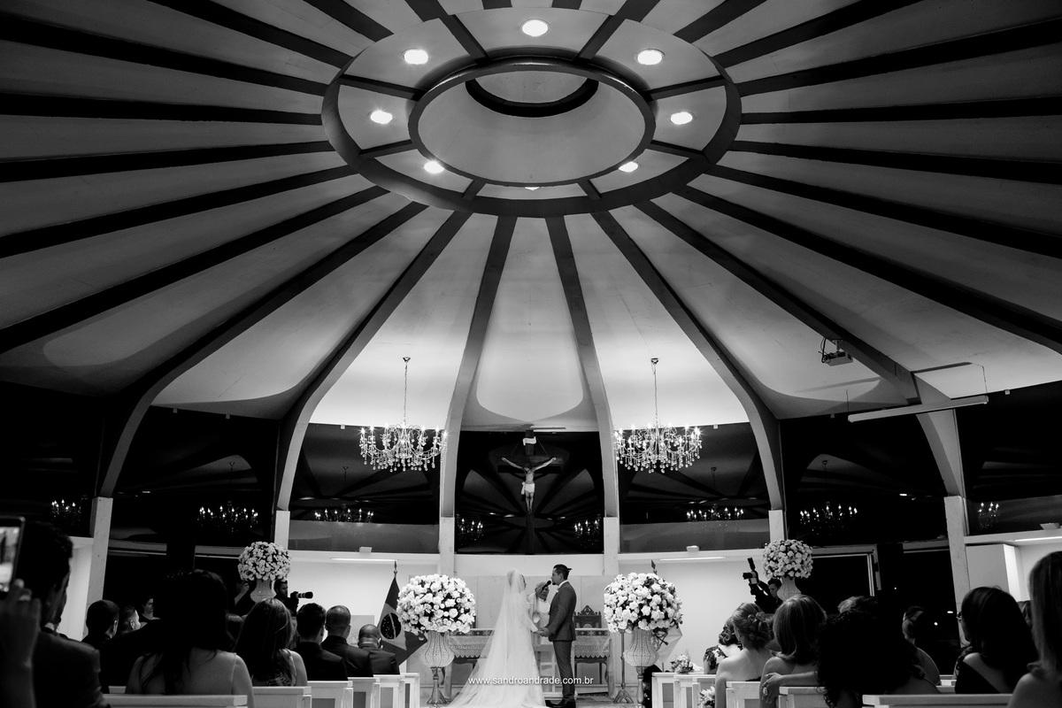 Linda fotografia preto e branco com a arquitetura magnifica da igreja e os noivos no altar se dão as mãos para o sim.