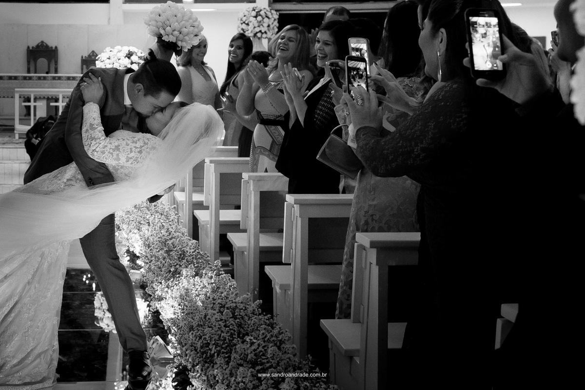 Beijo dos noivos durante a saida deles, ele joga sua amada em seus braços e a beija.
