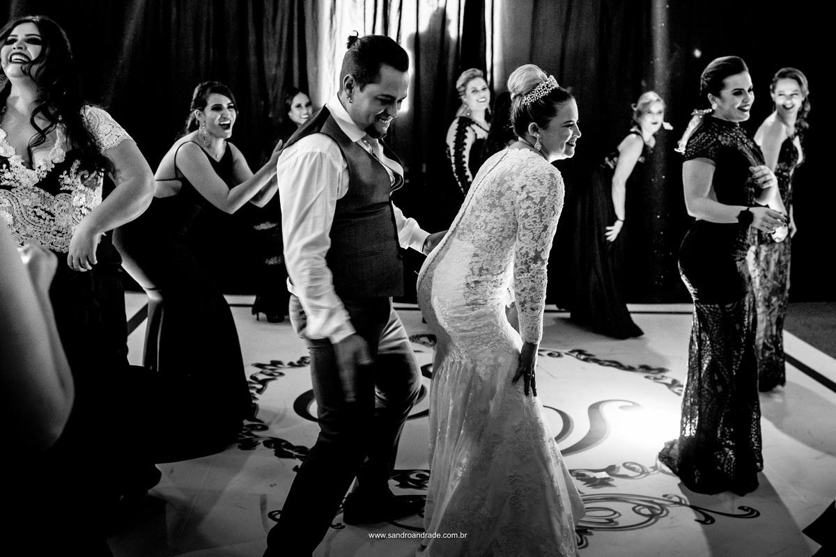 Dançando com as madrinhas, ele vai até sua esposa e a admira.