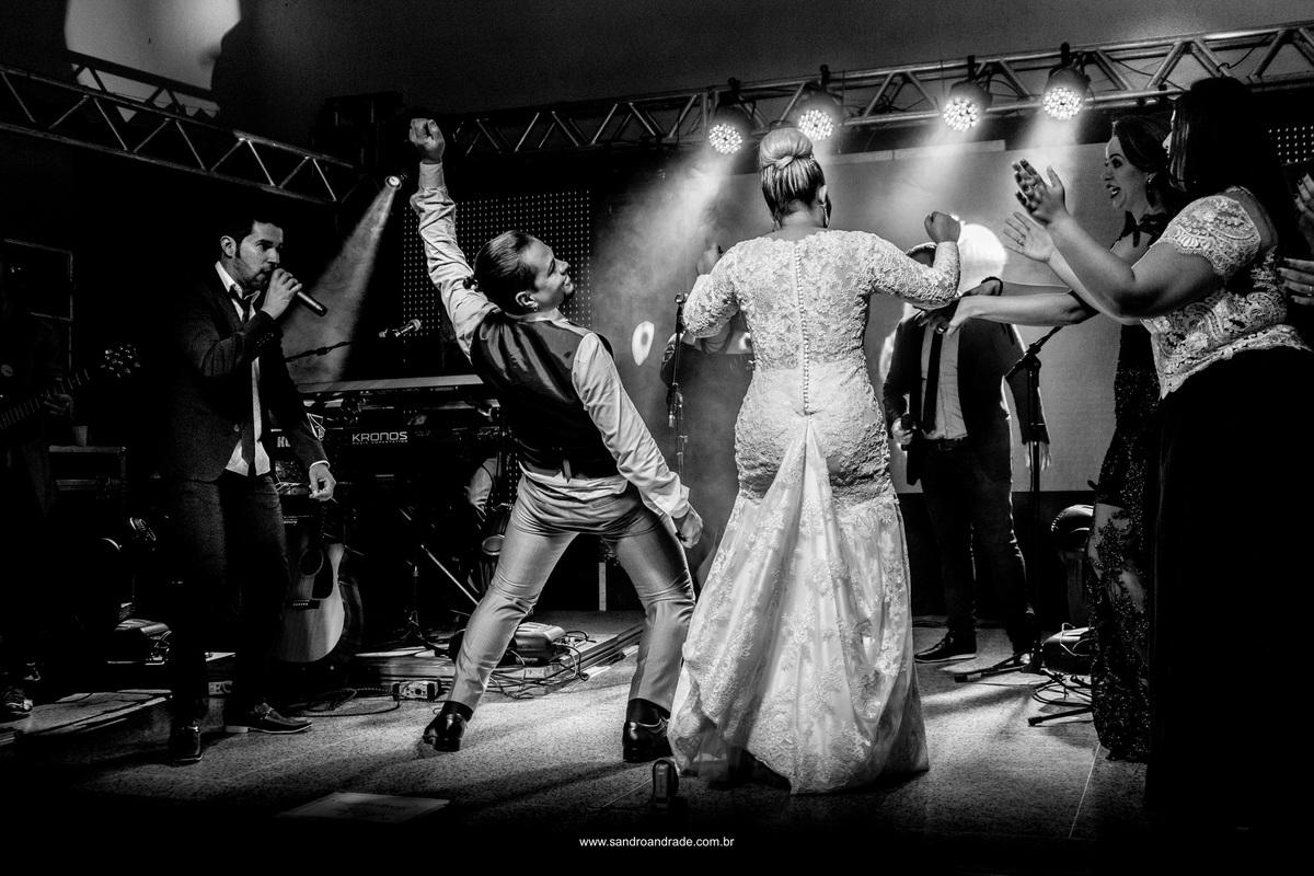 Os noivos em uma fotografia descontraida dançando no palco da festa.