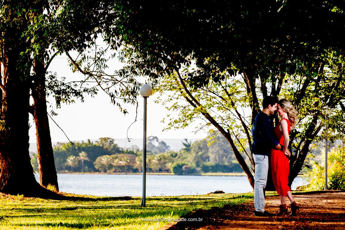O casal apaixonado em uma belissima fotografia colorida a beira do lago.