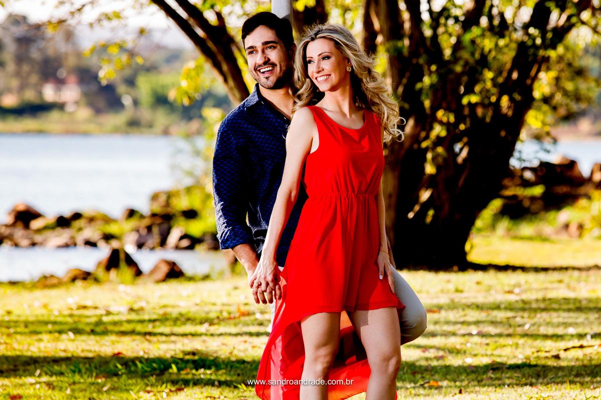 O belo casal sorridente em um belo contraste, ele de azul royal e ela em um belissimo vestido vermelho