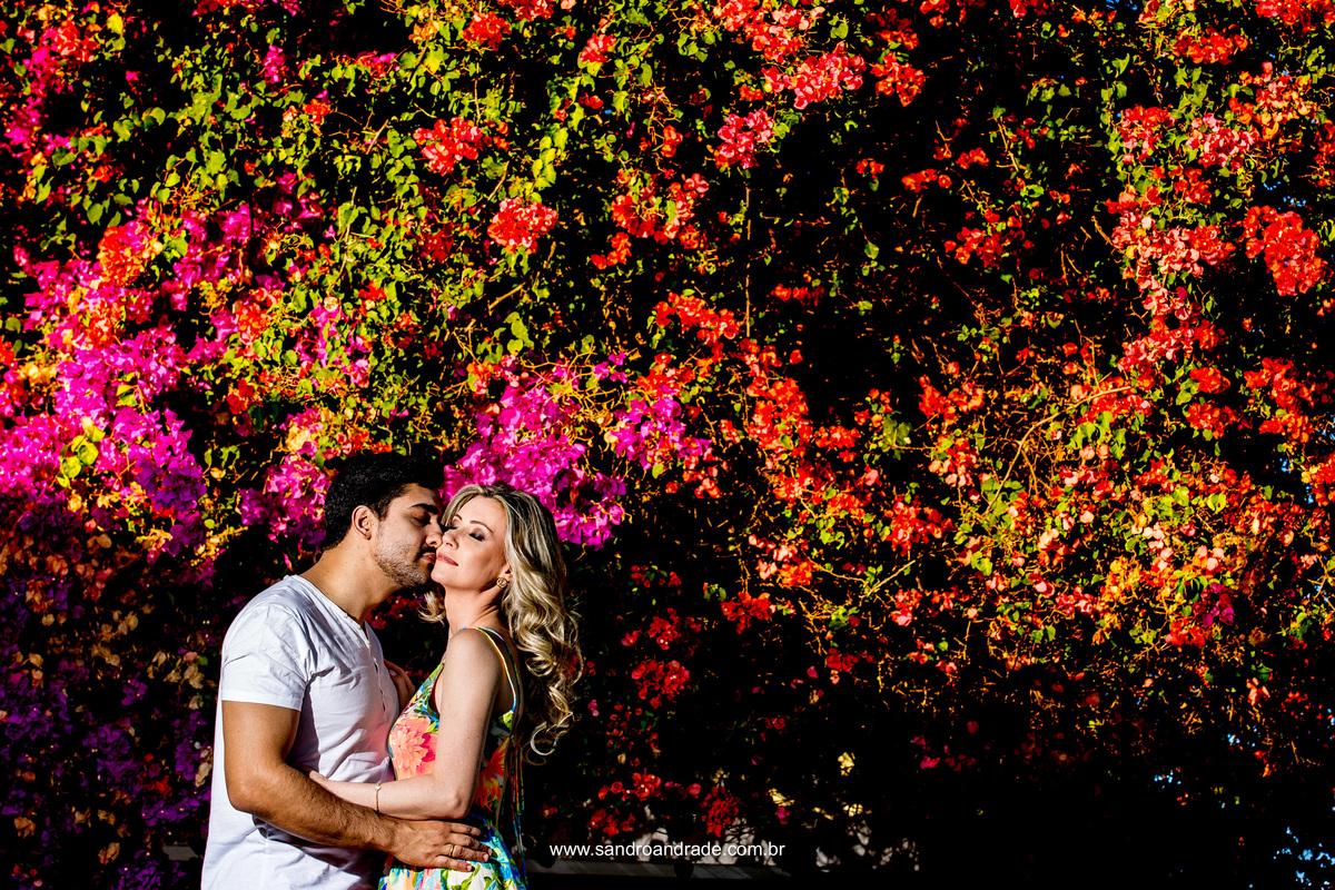 Muitas flores coloridas, um casal amoroso e um singelo beijo no rosto